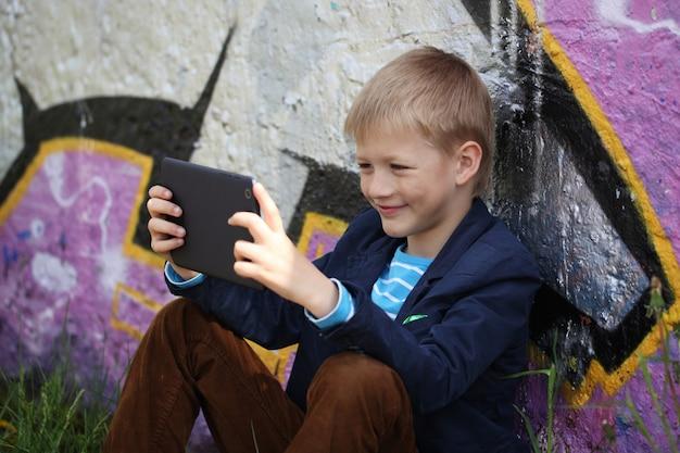 Kleiner junge in seine tablette zum lernen und spielen aufgenommen.
