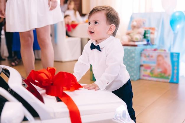 Kleiner junge in stilvollen kleidern, die lächelnd und nahe am auto stehen