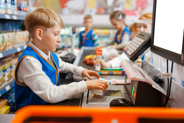 Kleiner junge in uniform an der kasse, der verkäufer spielt