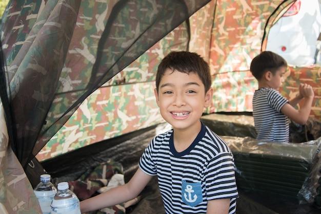 Kleiner junge innerhalb der kampierenden sommerzeit des zeltes tätigkeit im freien