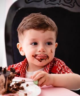 Kleiner junge isst kuchen und wird schmutzig
