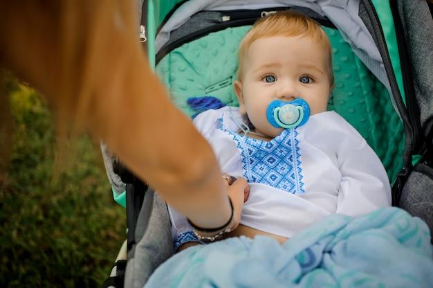 Kleiner junge kleidete im gestickten hemd an, das im kinderwagen mit einem friedensstifter liegt
