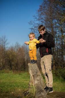 Kleiner junge kleinkind steht auf einem baumstumpf, vater unterstützt ihn vor dem hintergrund des waldes.
