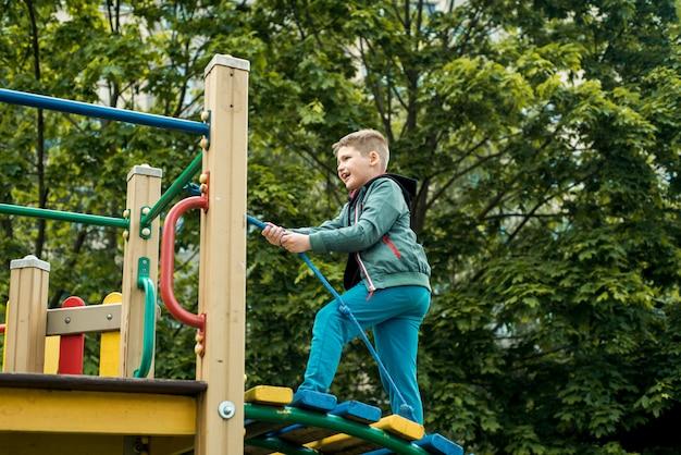 Kleiner junge klettert seil auf dem spielplatz im freien. ein junge von 6-7 jahren auf einem spielplatz klettert auf ein seil, lustige kindheit im kindergarten und in der schule, ein spaziergang im sommer.