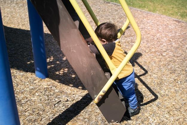 Kleiner junge klettert treppe im spielplatz hinauf