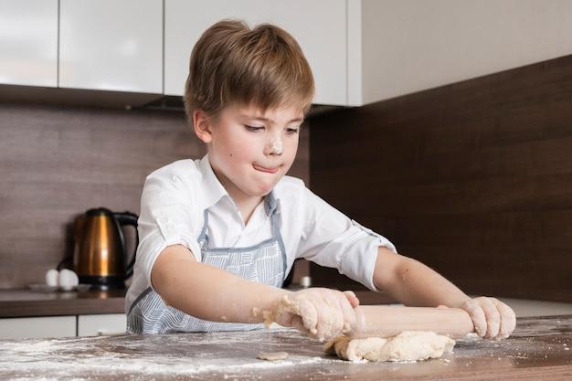 Kleiner junge konzentrieren sich, um teig zu rollen