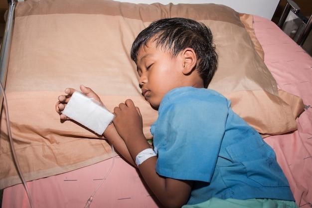 Kleiner junge krank im krankenhaus mit kochsalz intravenös