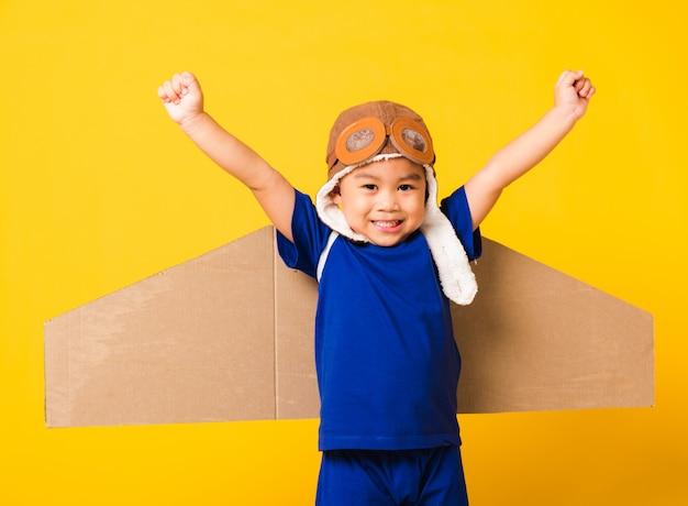 Kleiner junge lächelt und trägt pilotenhut und schutzbrille mit flugzeugflügeln aus spielzeugkarton