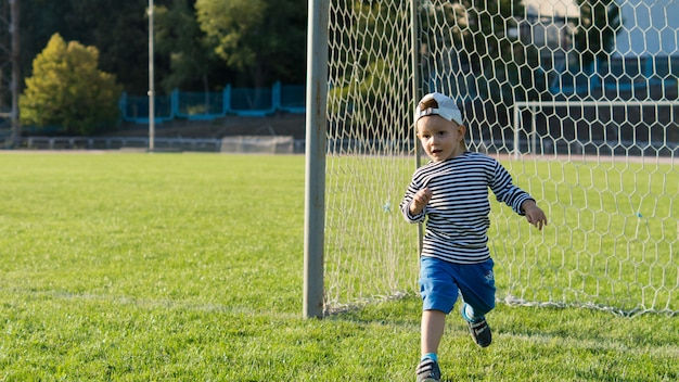 Kleiner junge läuft auf einem fußballplatz, der die torpfosten schützt, während er spaß hat, seine freiheit zu genießen