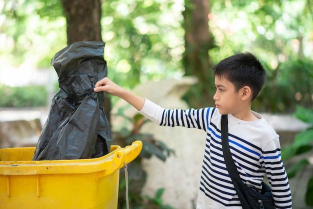 Kleiner junge legte den schwarzen müllsack in den müll