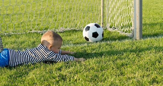 Kleiner junge liegt ausgestreckt auf dem grünen gras in den toren, als er den fußball verfehlt, während er torhüter spielt