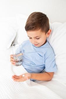 Kleiner junge liegt krank im bett und hält eine tablette und ein glas wasser