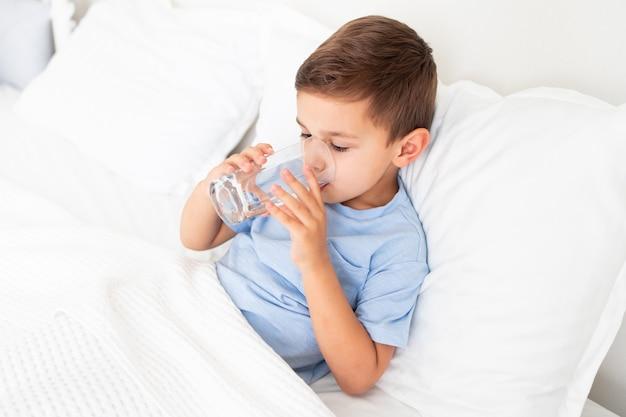 Kleiner junge liegt krank im weißen bett und trinkt wasser