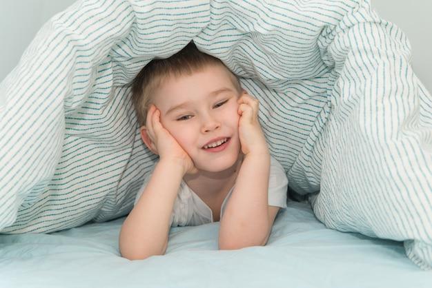 Kleiner junge liegt unter der decke und lächelt