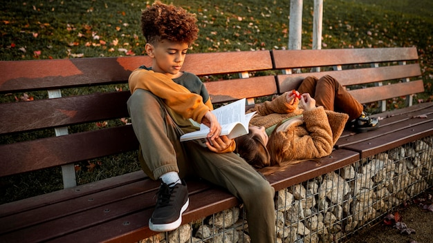 Kleiner junge liest auf einer bank neben seinem freund