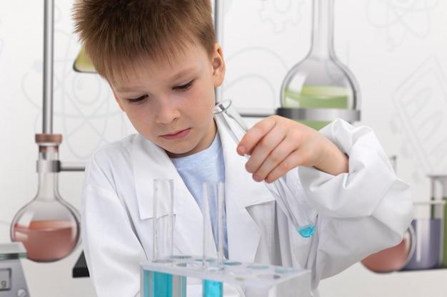 Kleiner junge macht ein wissenschaftliches experiment in der schule