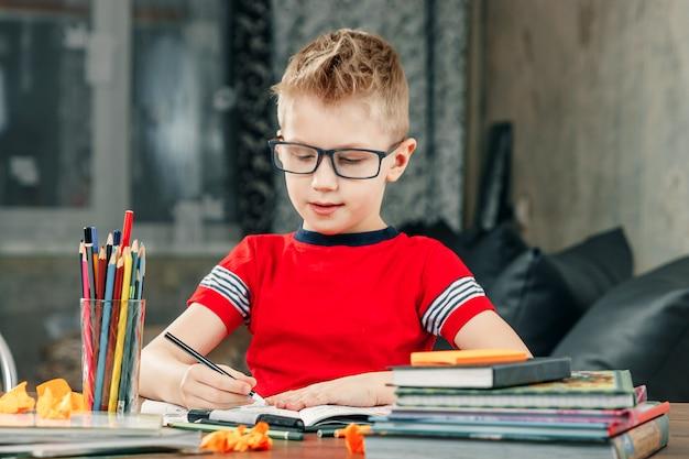 Kleiner junge macht hausaufgaben in der schule.