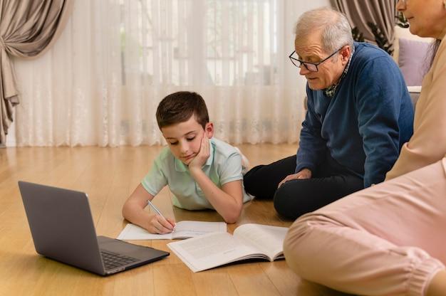 Kleiner junge macht hausaufgaben mit seinem großvater zu hause