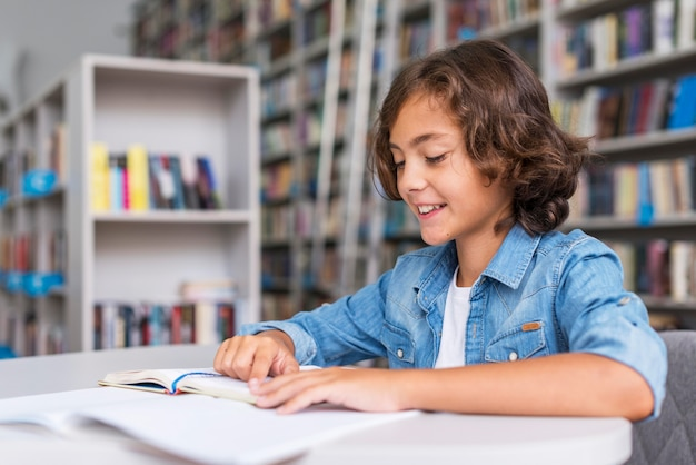 Kleiner junge macht seine hausaufgaben in der bibliothek