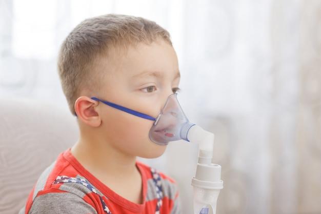 Kleiner junge macht therapeutische inhalation