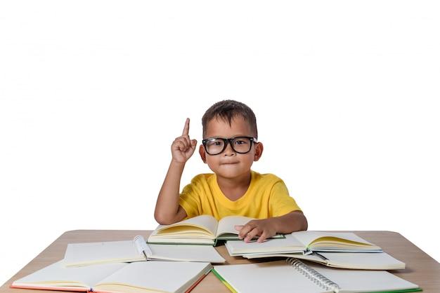 Kleiner junge mit brille dachte und viele bücher auf dem tisch. zurück zum schulkonzept, isolat