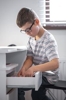 Kleiner junge mit brille sitzt an seinem schreibtisch vor einem laptop und sucht etwas in einer schublade.
