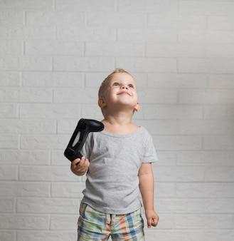 Kleiner junge mit dem steuerknüppel, der oben schaut