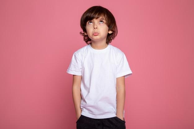 Kleiner junge mit den händen in seiner tasche weißes t-shirt und blaue jeans, die das celing auf rosa schreibtisch betrachten