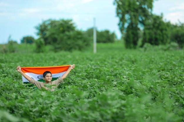 Kleiner junge mit der indischen flagge in der natur