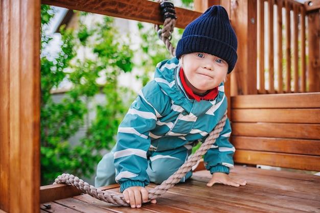 Kleiner junge mit down-syndrom spielt auf dem spielplatz, selektiver fokus
