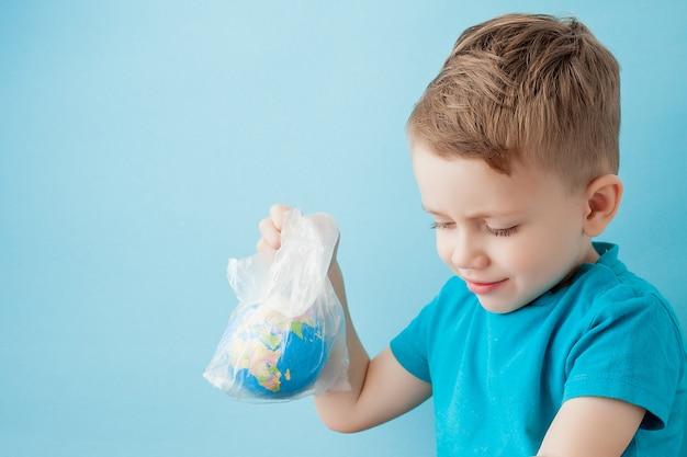 Kleiner junge mit einem globus in einem paket auf einem blauen hintergrund