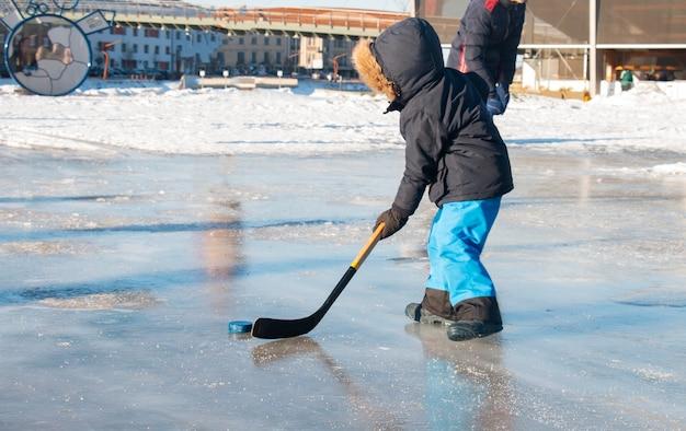 Kleiner junge mit einem hockeyschläger, der hockey spielt