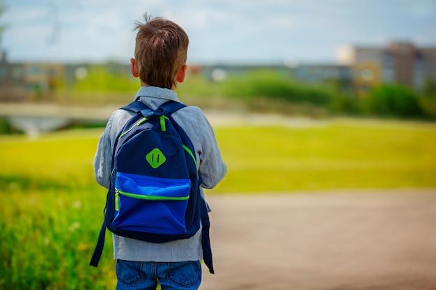 Kleiner junge mit einem rucksack zur schule gehen. rückansicht