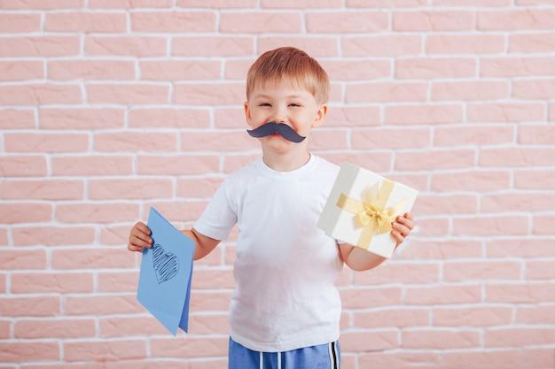 Kleiner junge mit einem schnurrbart, der ein geschenk in seinen händen hält