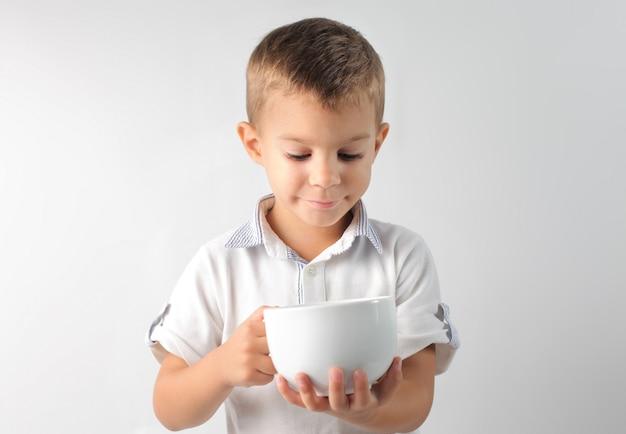 Kleiner junge mit einer großen tasse