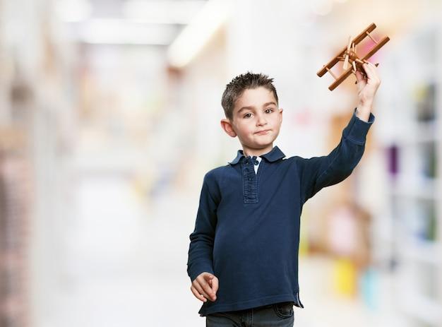 Kleiner junge mit einer holz-flugzeug spielen