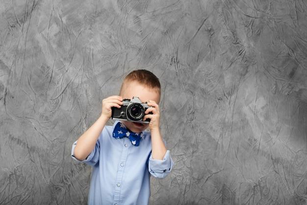 Kleiner junge mit einer retro-filmkamera