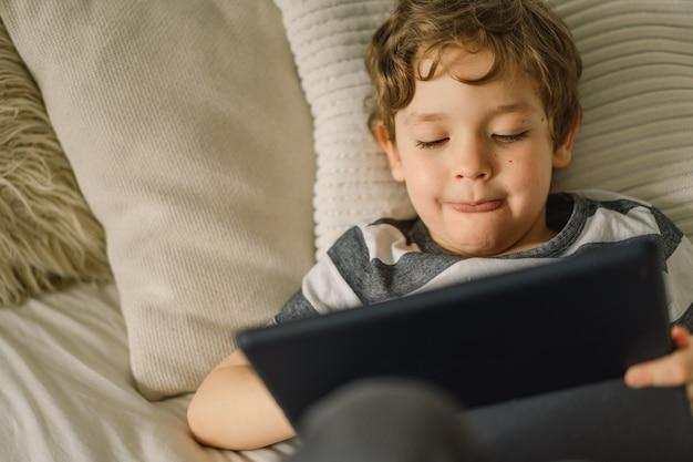 Kleiner junge mit einer tablette im zimmer
