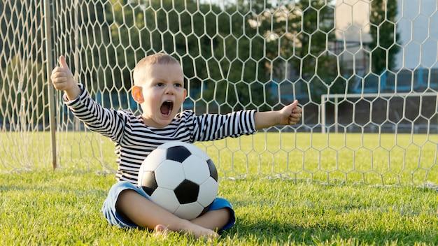 Kleiner junge mit fußball oder fußball auf seinem schoß, der im tor sitzt und vor aufregung seine arme winkt