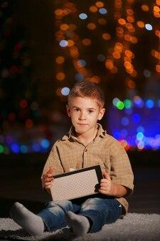Kleiner junge mit geschenkbox auf einem unscharfen dunklen hintergrund