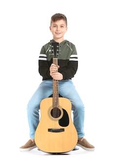 Kleiner junge mit gitarre auf weißer oberfläche