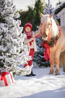 Kleiner junge mit gläsern streichelt entzückendes pony mit festlichem kranz nahe dem kleinen holzhaus und den schneebedeckten bäumen
