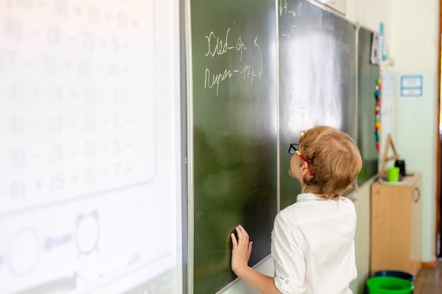 Kleiner junge mit großen schwarzen gläsern und dem weißen hemd, die nahe schultafel mit einem stück kreide intelligentes denkendes gesicht machend steht