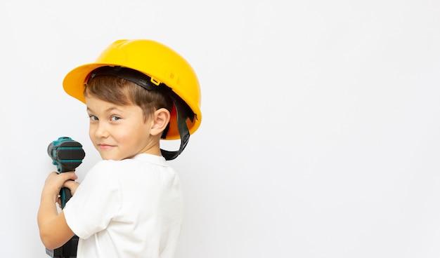 Kleiner junge mit heimwerkerwerkzeug zu hause kleiner baumeister im helm mit einem bohrer und sah die arbeit des denkens über die zukunft