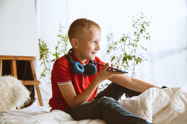 Kleiner junge mit intelligenten uhren, smartphone und kopfhörern