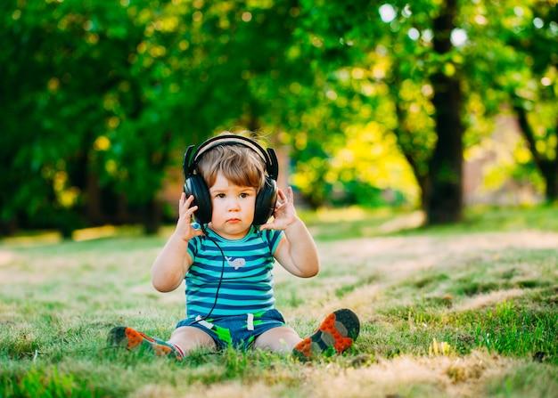 Kleiner junge mit kopfhörer.