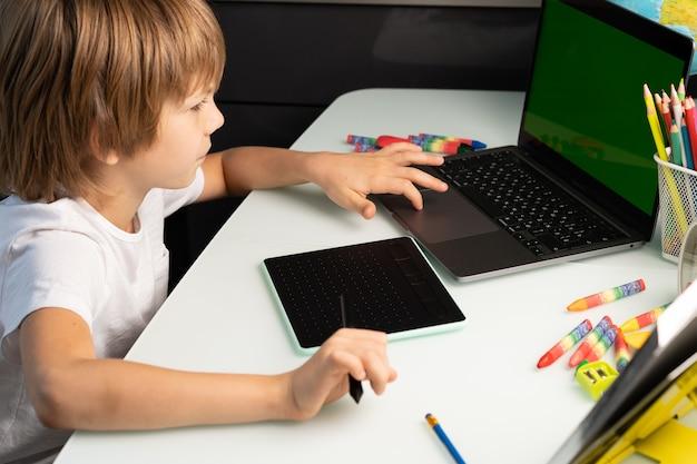 Kleiner junge mit laptop und grafiktablett grün chromakey auf laptop