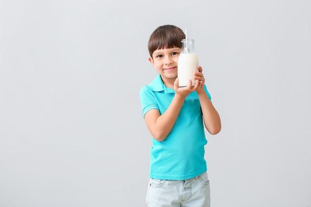 Kleiner junge mit milch auf licht