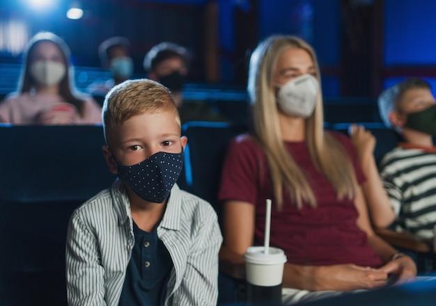 Kleiner junge mit mutter, die im kino auf die kamera schaut, filme anschaut und coronavirus-konzept.