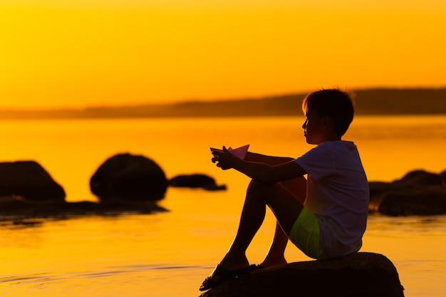 Kleiner junge mit papierschiff in den händen. schöner orangefarbener sonnenuntergang. origami. fluss. see.